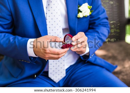 the groom in a blue suit holding box with wedding rings - stock photo