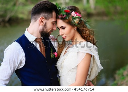 the groom in a wedding suit and the bride in lace dress with bouquet and wreath in the forest - stock photo