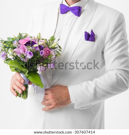 the groom in a white suit holding a wedding bouquet - stock photo