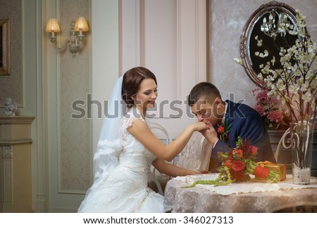 The groom kisses the bride's hand in a beautiful interior