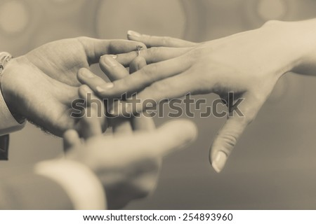 The groom puts a wedding ring on bride's finger, gently. Macro frame of hands newlyweds in sepia tone. - stock photo