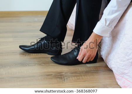 The groom puts on shoes
