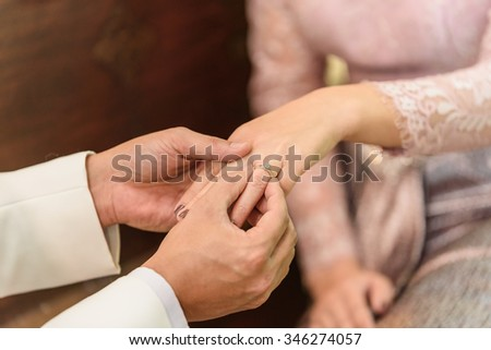 The groom puts the wedding ring to finger of the bride