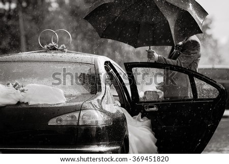 the groom sees the bride in the car, rain during the wedding, black and white wedding photography, wedding photography conceptual groom holding an umbrella, wedding gown - stock photo