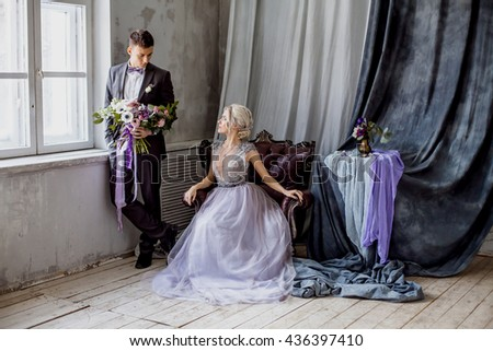 the groom standing at the window, the bride sits