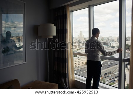 The groom stands near window