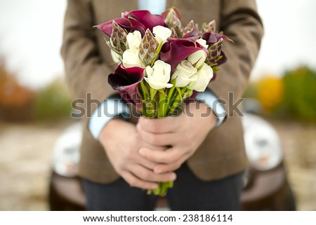The groom waits bride with a bouquet. Close-up of hand with a bouquet. Focus on the flowers. - stock photo