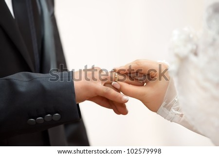 The groom wears a ring bride - stock photo