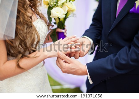 The groom wears the ring bride at a wedding ceremony. - stock photo