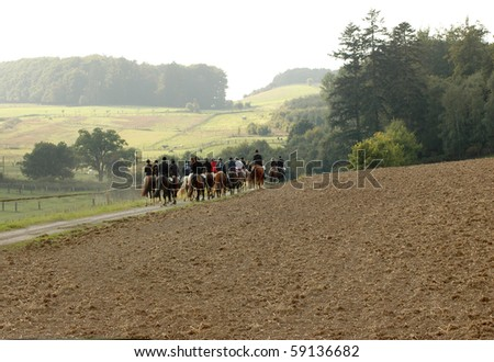 The group of equestrians ride through the field.