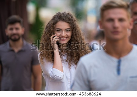 The group of people stand behind each other. Girl talk to the phone - stock photo