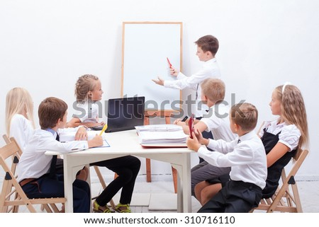 The group of teenagers sitting in a business meeting on white background - stock photo