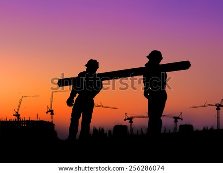 The group of workers working over blurred construction site. - stock photo