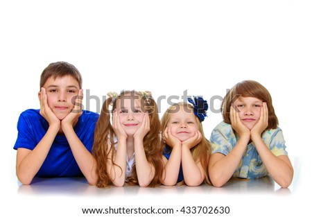 The group, two girls and two boys, all four people lying on the floor resting head on hands-Isolated on white background - stock photo
