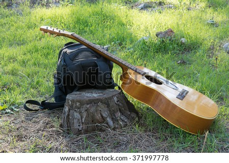 The guitar and backpack on a green clearing in the woods near the old stumpThis photo is correcting  - stock photo