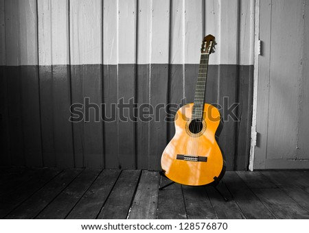The guitar on the old wooden wall, color in black - stock photo