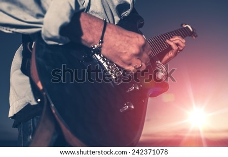 The Guitarist. Guitarist Playing on the Electric Guitar at Sunset. Closeup Photo. - stock photo