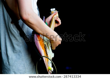 The Guitarist. Guitarist Playing on the Electric Guitar with black background.  - stock photo