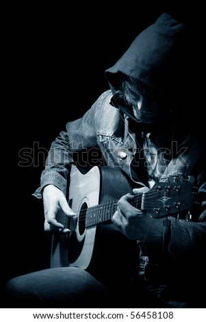 The guitarist plays an acoustic guitar - stock photo