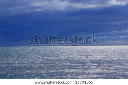 The Gulf St Vincent with an approaching rain front, featuring a cargo ship on the horizon (Adelaide, Australia). - stock photo