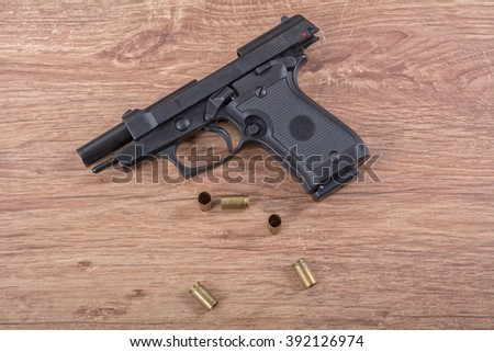 The gun with the bullets on a brown wooden background - stock photo