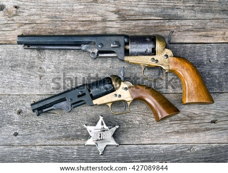 The guns that won the west and silver sheriff badge. - stock photo