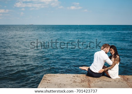 The guy and the girl are sitting on the pier by the sea