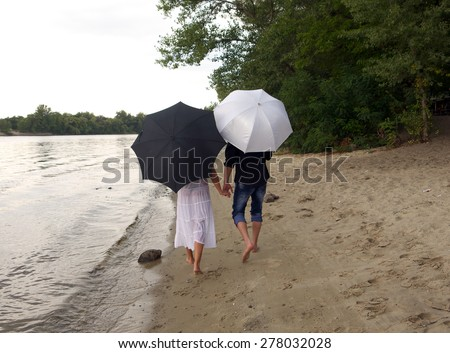 the guy and the girl are under umbrellas on the river bank - stock photo