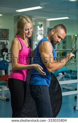 The guy and the girl at the gym doing the exercises. Help and control the performance of complex exercises. Photos for sporting magazines, posters and websites.