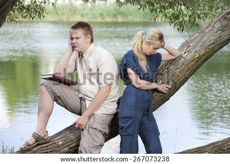 The guy and the girl in quarrel on the bank of the lake - stock photo