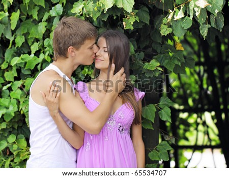 The guy and the girl kiss in park against green foliage