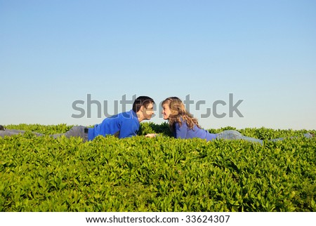 The guy and the girl lay in a grass and look against each other - stock photo
