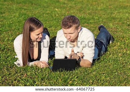 The guy and the girl lie in park on a grass with the laptop