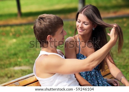The guy and the girl on a bench in city park - stock photo