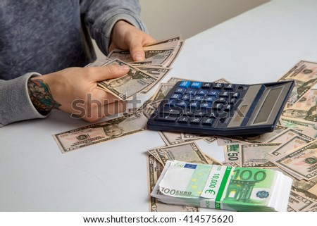the guy at the desk considers on the calculator a lot of money in the currency of the dollar and the euro - stock photo