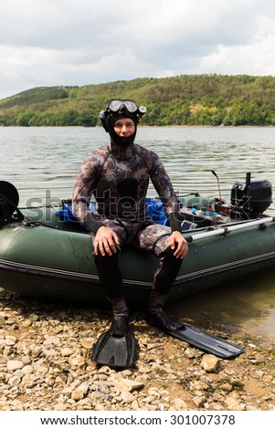 The guy in a diving suit. Diving, diving in the river. Suit for spearfishing. Spearfishing.