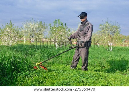 The guy in dark glasses mowing grass in the garden - stock photo