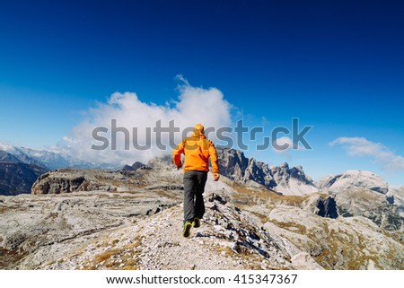 The guy in the orange jacket and sneakers running trails in the mountains