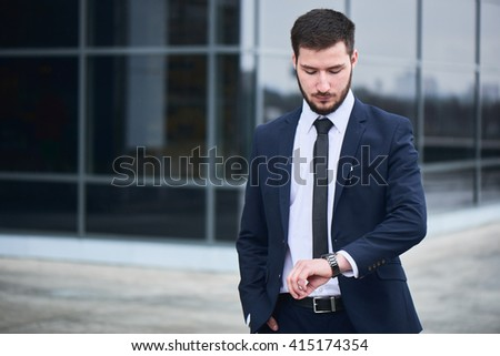 The guy in the suit looks at his wristwatch against the building with a glass facade