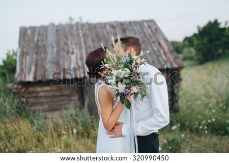 the guy in the white shirt and the girl in white dress kissing on the background of a wooden house in a field - stock photo
