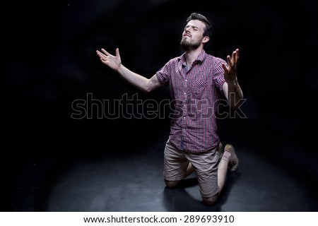 the guy is on his knees and prays to God - stock photo