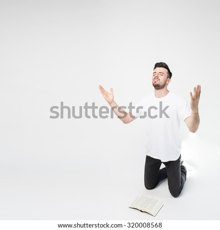 the guy is on his knees and prays to God and read?ng Bible - stock photo