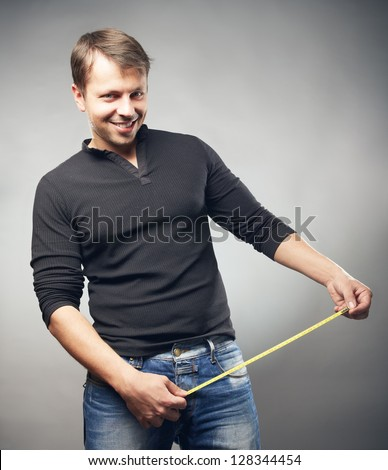 The guy measures the penis sizes by a ruler - stock photo