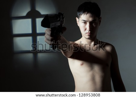 The guy of the Asian appearance bared on a belt aims a pistol - stock photo