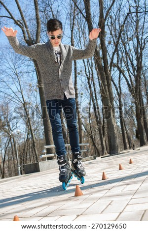 The guy on roller skates. Man riding between cones on roller skates - stock photo