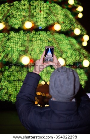 The guy photographs a New Year tree on the smartphone - stock photo