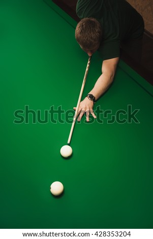 The guy plays billiards and aim the ball in the hole. Focus on center of photo. View from above. Empty space for text. - stock photo