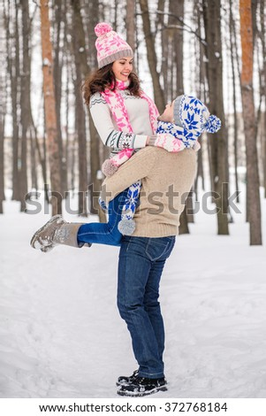The guy raised his beloved girlfriend to the hands and spins, winter outdoors. - stock photo