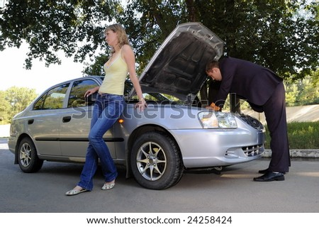 The guy repairs the car, the girl stands nearby - stock photo