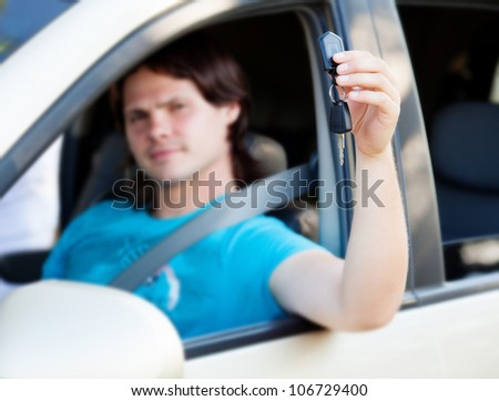 the guy sitting in the car with the keys in the hands - stock photo